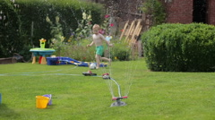 Boy playing with garden sprinkler, slow motion HD Stock Footage