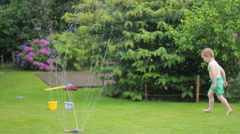 Happy little boy playing and splashing with a garden sprinkler, slow motion HD Stock Footage