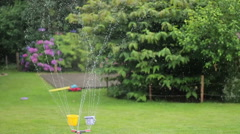 Automatic garden lawn sprinkler in action watering grass, slow motion HD Stock Footage