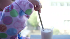Little girl child in cafe licks the tube from a milkshake - kid drinking milk Stock Footage