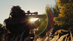 Sniper in camouflage clothing takes aim. The sun's rays shine through in the Stock Footage