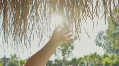 A little girl playing in the sun touching the roof bungalows with grass. The sun Stock Footage