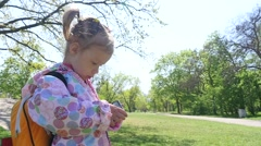 Little girl during walking in park stay typing watching smart phone cartoons  Stock Footage