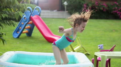 Little girl in a colorful swimming suit jumps into the pool, slow motion HD Stock Footage