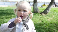 Little kid girl drinking a pure fresh water from a nippled bottle Stock Footage