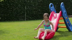 Girl having fun with garden sprinkler and children's slide, slow motion HD Stock Footage