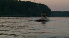 Wakeboarder girl stars riding from lake water on sunset Stock Footage