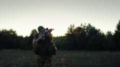 Steadicam shot: Soldier in camouflage attack. In the rays of a sunset in arms Stock Footage
