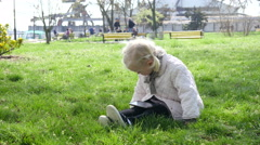 Cute little girl watching cartoons on smart phone sitting on grass in park Stock Footage