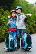 Happy kids standing near mono-wheel hoverboard or gyroscooter outdoor Stock Photos