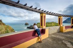 Woman looking at the ocean from special viewpoint spot in Porto da Cruz, Madeira Stock Photos