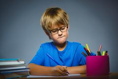 School concept. doubt, expression - boy thinking over gray background Stock Photos