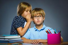 School Communication concept. girl whispering in ear of boy Stock Photos