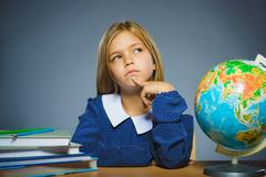 School concept. girl thinking or sitting at the desk in the classroom Geography Stock Photos