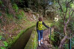 Woman walking on levada 25 fountains in Rabacal, Madeira island Stock Photos