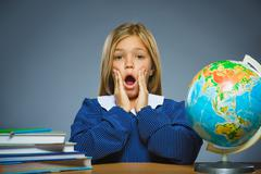 School concept. girl with astonished or doubt expression sitting at desk Stock Photos