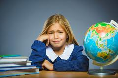 School concept. crying girl with astonished or doubt expression sitting at desk Stock Photos