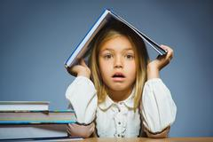School concept. doubt girl sitting at desk and holding book on her head Stock Photos