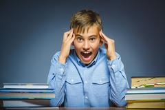 School concept. doubt or angry boy sitting at desk Stock Photos