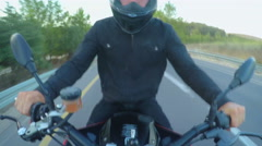 Motorcycle rider driving on a curved countryside road Stock Footage