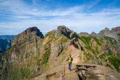 Woman hiker on the dangerous path between the rocky cliffs of Pico Arieiro Stock Photos