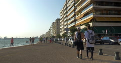 Two young boys walk along the seafront of Thessaloniki, Greece Stock Footage