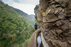 Woman walking at footpath along the rocky cliffs. Levada Nova hike, Madeira Stock Photos