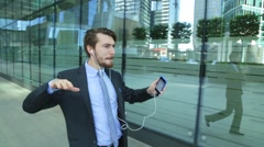Man is wearing suit listening to music in headphones, walking, dance, singing Stock Footage