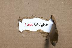 The word lose weight appearing behind torn paper Stock Photos