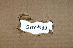 The word strategy appearing behind torn paper Stock Photos