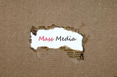 The word mass media appearing behind torn paper Stock Photos