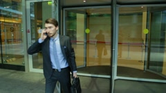 Man is coming out of the glass revolving doors, talking on the phone, in a hurry Stock Footage