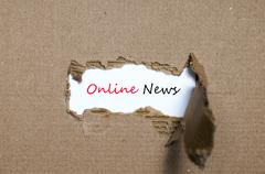 The word online news appearing behind torn paper Stock Photos