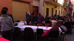 Small city street blocked with many tables, Spanish citizens have outdoor repast Stock Footage