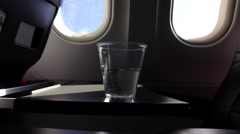 Plastic glass with water stand at folding table, airliner interior during flight Stock Footage