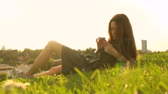 Beautiful brunette girl in black dress using her smartphone on the lawn. Leisure Stock Footage