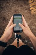 Female runner using a fitness app on her mobile phone Stock Photos