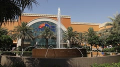 Front entrance to Deira City Centre mall, green square and fountain Stock Footage
