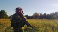 Steadicam shot: Armed man in a camouflage suit and weapons goes on a country Stock Footage