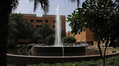 Fountain at small park square against Deira City Centre front entrance Stock Footage