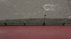 Gray water stream rush beside red tiled pavement, empty promenade Mzymta river Stock Footage