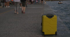 Suitcase on wheels stands on sea coast in city of Thessaloniki, Greece Stock Footage