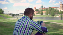 Young man watching photos, sitting on grass. Steadicam. Stock Footage
