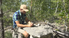 Tourist man He is sitting at a stone table and using smartphone . men with ba Stock Footage