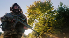 Man in camouflage with guns. It should be against the sky, the sun shines on his Stock Footage