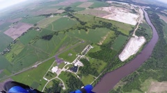 Professional skydiver parachuting in blue sky above green flatland and river Stock Footage