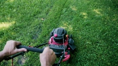 Walk near moving cut grass lawn cutter on garden meadow Stock Footage