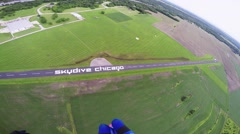 Professional skydiver parachuting in grey sky above green flatland. River Stock Footage