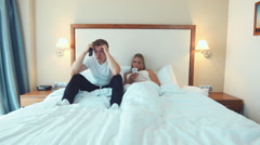 Overwhelmed man sitting in bed beside woman Stock Footage