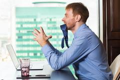Angry red haired businessman chewing his tie Stock Photos